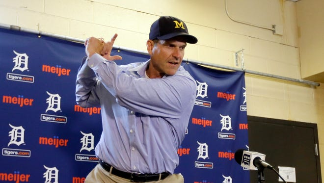 June 30, 2015: Michigan football coach Jim Harbaugh shows the media his batting stance before throwing out the first pitch at a baseball game between the Detroit Tigers and the Pittsburgh Pirates.