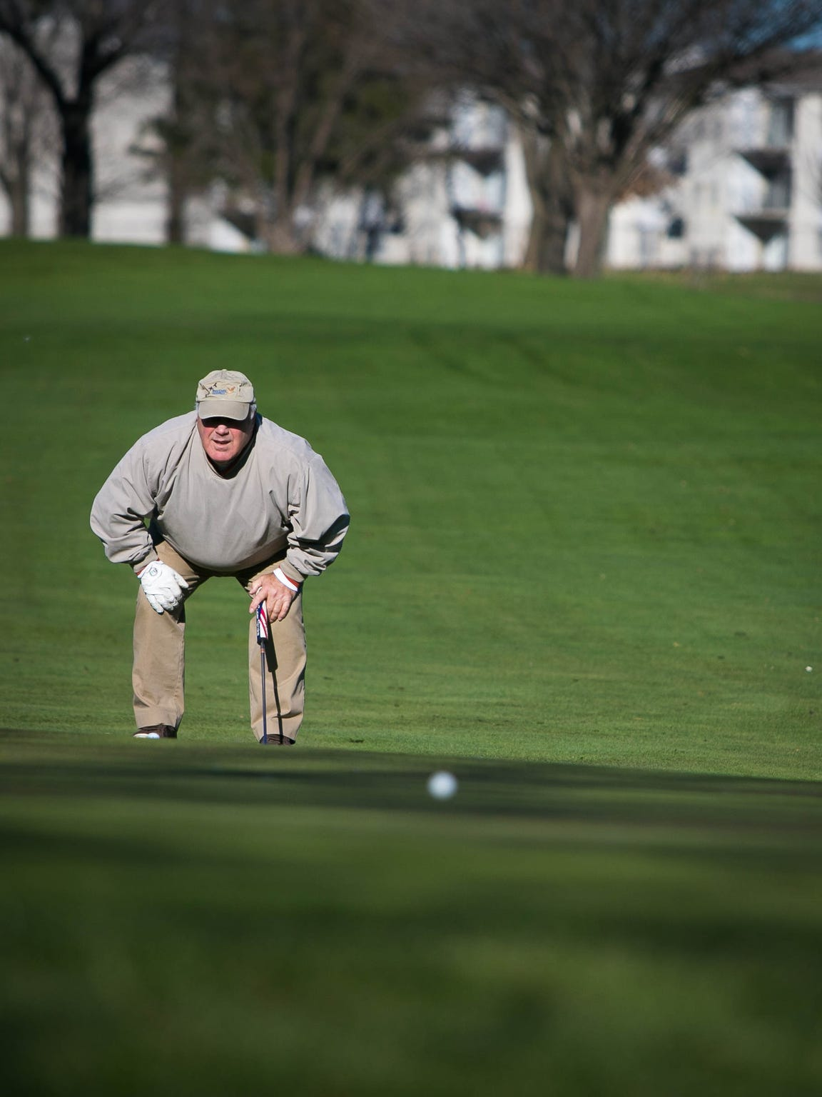 Club member Fran Long checks his line at the putting green on the back nine at Cavaliers Country Club. The club is still taking members, but is the subject of a redevelopment proposal.