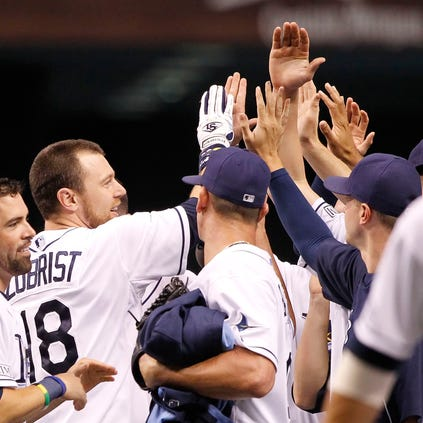 Tampa Bay Rays second baseman Ben Zobrist (18) is congratulated by teammates after he hit the game winning RBI single during the ninth inning against the New York Yankees at Tropicana Field. Tampa Bay Rays defeated the New York Yankees 1-0.