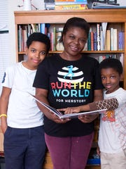 Valeria Haley and sons, Virgil Johnson Jr. (left) and Jontue Johnson Jr. (right), stand in front of their book collection at home. Reading is now a huge part of their family's life.