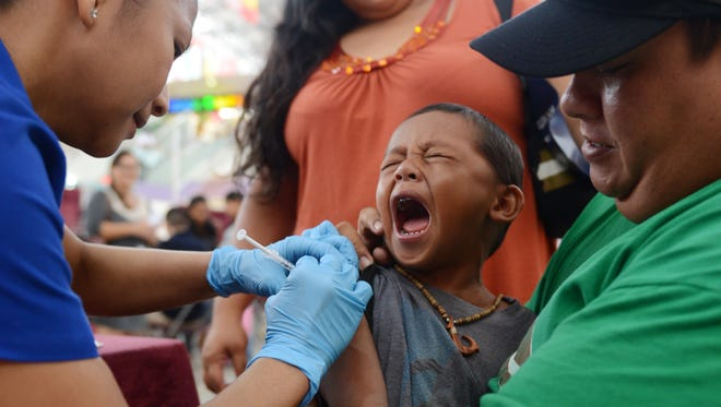 In this file photo, a child gets a vaccination at a back-to-school immunization outreach clinic held by the Department of Public Health and Social Services at the Micronesia Mall.
