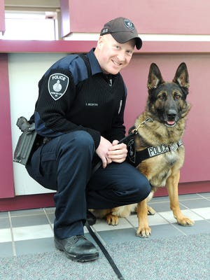 Officer Charles Beckford poses with K-9 Rony.