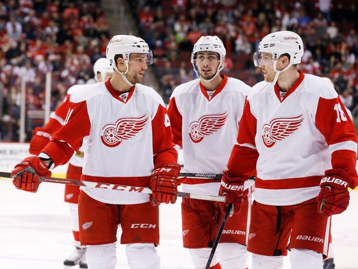 Red Wings forward Luke Glendening, left, talks with