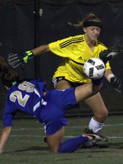 Brentwood's Hayley Jordan falls to the ground as Hendersonville goalkeeper Makensie Cotter goes for the save during Tuesday's match.