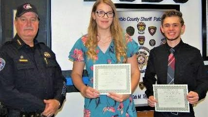 Pueblo County Sheriff Kirk Taylor, left, poses with recipients of his office's scholarship: Cierra Dobney, center, and Luke VanBuskirk.