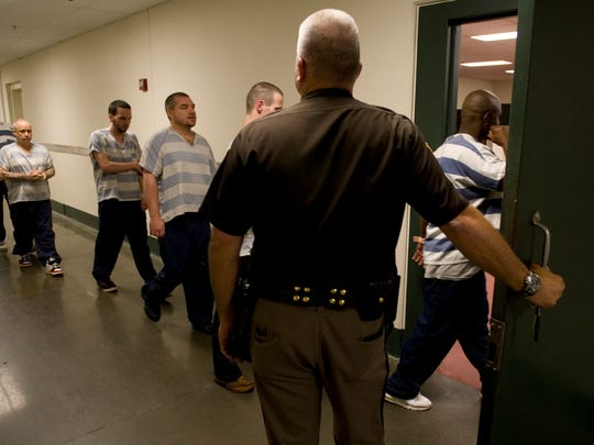 Vanderburgh County Sheriff Eric Williams holds the door for inmates heading to work in the jail's kitchen Wednesday, May 14, 2014.