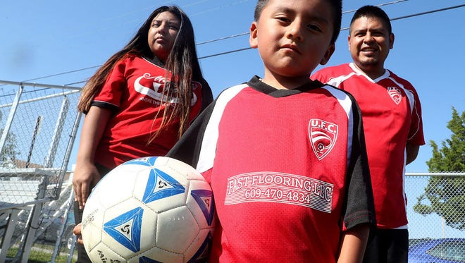 In this Saturday, Sept. 16, 2017, photo, Gregorio Huestipa, 35, his 15-year-old daughter, Stephanie, and son, Brian, 4, of Pleasantville, pose for a photo as they get ready to play a community soccer game. Huestipa is dealing with a threat of immigration deportation ICE arrested Gregorio over the summer for living here illegally and held him in jail in Newark for more than a month.