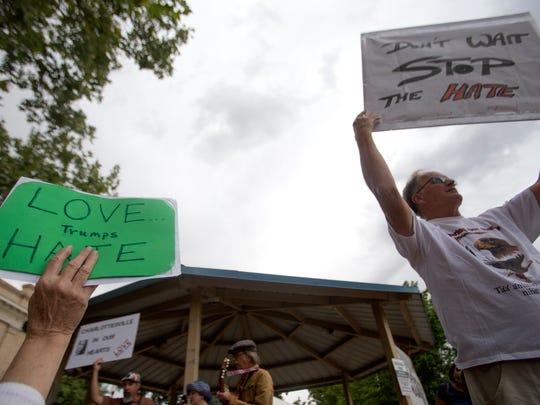 At right, John Carlson participates in a vigil for the victims of Charlottesville Virginia Tuesday in Farmington.