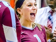 Brooke Bez ,1, of Okemos celebrates after she and her teammates were awarded the CAAC Blue chanpionship trophy after the win over Holt Tuesday  in Okemos.