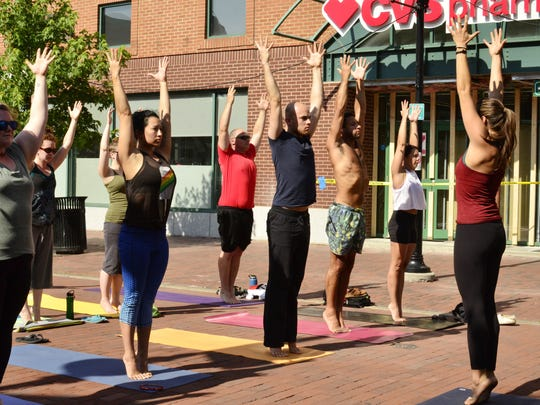 Yoga instructor Mackenzie Doyle, right, leads participants in a class on Sunday, June 18, 2017, on Church Street in Burlington.
