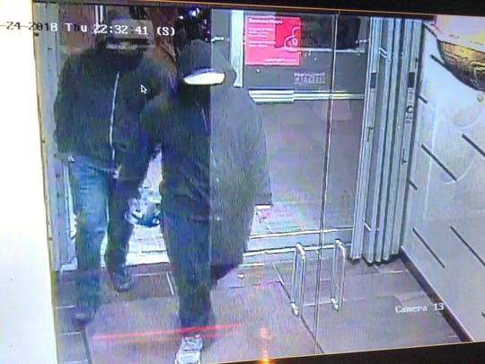 In this image made from CCTV footage released by Peel Regional Police, two suspects enter a glass doorway of the Bombay Bhel Indian restaurant, late May 24, 2018, in Mississauga, suburb of Toronto, Canada.