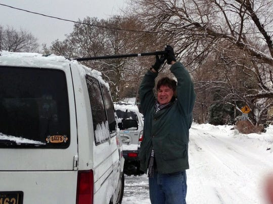 """Michael Davis, of Bellefonte, cleans off the roof of his SUV in what has become a ritual this winter. """"I got to find some beauty in it"""" he said."""