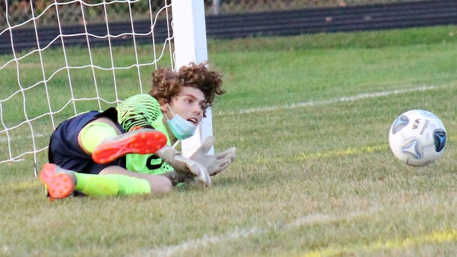 Exeter keeper Johnny Meyer comes up with a diving save on a penalty kick late in the Exeter boys soccer team's 2-1 win over Dover on Tuesday at Dunaway Field.