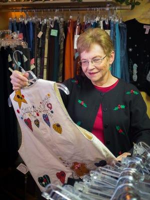 La Tienda de Jardin Ladies Boutique volunteer of 5 years Sue Fletcher looks at a Christmas-themed vest at the store.