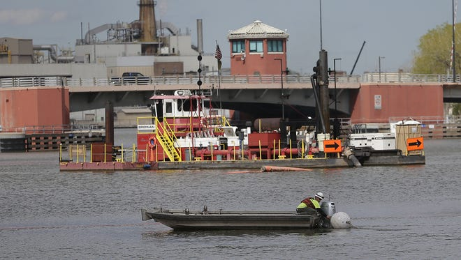 Brennan Marine employees work from a dredging barge removing PCBs from the Fox River just south of the Ray Nitschke Memorial Bridge in downtown Green Bay.