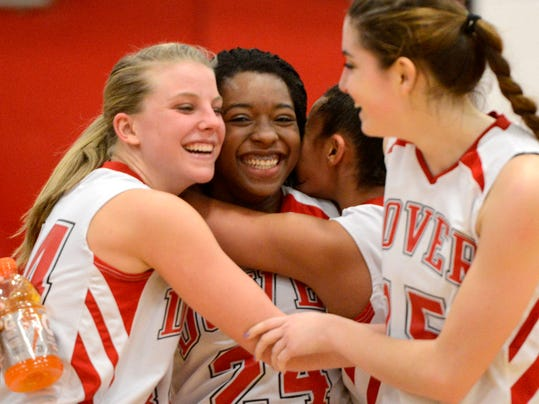 Alayah Hall, center, is embraced by teammates after scoring her 1,000th career point Monday in Dover's District 3 Class AAAA first-round win vs. Governor Mifflin. (Daily Record/Sunday News -- Kate Penn)