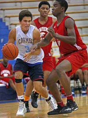 Carmel's #3 Sam Oliphant moves past Lawrence North's #22 Kevin Easley and #52 Ra Kpedi during the 11th Annual Charlie Hughes High School Shootout at Carmel High School, Sunday, June 21, 2015.  Lawrence North won the championship game.