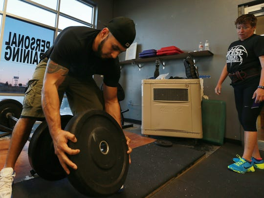 Paula Powell watched trainer Jonathan Ramos add more weight to the bar during a workout at Sho Offz Fitness.