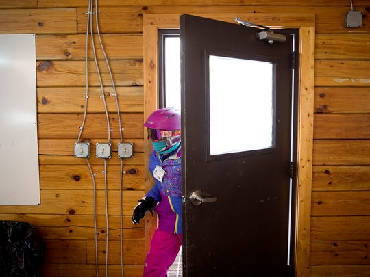 A French Broad River Academy student walks into the group lodge from the frigid elements Feb. 9, 2017 at the Cataloochee Ski Area in Maggie Valley. The Girls French Broad River Academy is a school that emphasizes outdoor learning, through field lessons such as skiing, canoeing, hiking, and public service.
