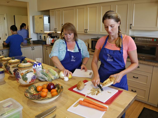 Nicole Lupica , r, peels potatoes while Sarah Frew helps to assemble soup components  at the Ryan House kitchen. They are member sod the Soup Troop, who makes soup for Hospice patients, as seen in Phoenix, on Sept. 23, 2014.