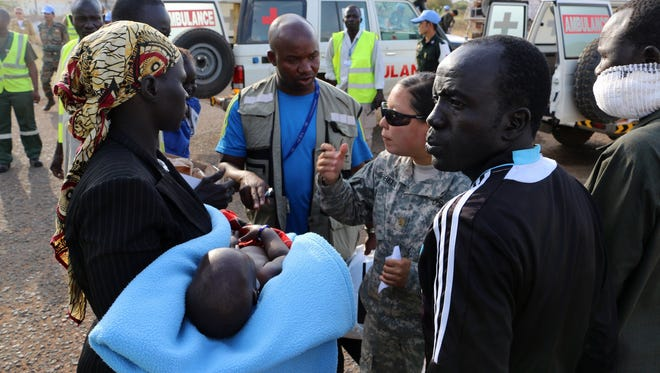 A handout photo released by the UNMISS shows a woman carrying a baby as a group of wounded people were transported from Bor to Juba on Dec. 22.