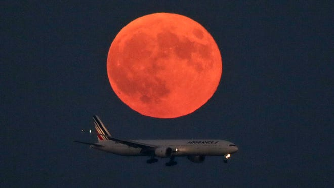 An Air France jetliner is approaches to  land under the Supermoon' at the Tokyo International Airport.