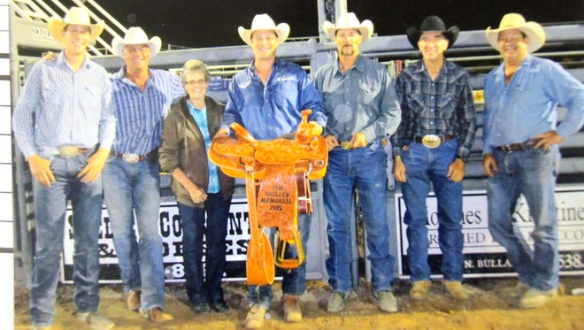 For the first time since the Jimmy Shelley Memorial roping competition began in 1999 at the Grant County Fair, the prize saddle was won by one of Jimmy Shelley's grandsons, Aaron Shelley. The Shelley family has ranched in the Cliff area since 1884. Pictured are, from left, Holt Shelley, Troy Shelley, Leeann Thorp, Aaron Shelley, Dale Shelley, Terrell Shelley and Keith Wilkerson.