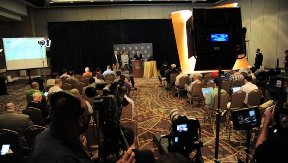 A press conference is held in a ballroom inside the