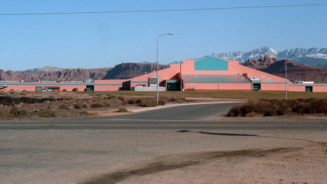 In early 1993, the best guess of when the Spectrum and Daily News file image was taken based on other images captured on the same roll of film, Snow Canyon Middle School was the newest school building in the Washington County School District having been built the year before in 1992. A year later, in 1994, Snow Canyon High School would open its doors just north of the middle school. In the now image, taken by Spectrum & Daily news photographer Jud Burkett, on the left side of the image just above the roof line of the middle school, the very top of the Snow Canyon High School gym can be seen. The intersection of Santa Clara Drive and the road that has come to be called Warrior Way now boasts a traffic light instead of a two-way stop sign, and on the very left side of the image, the sign for the Santa Clara Branch of the Washington County Library, a structure that did not exist in 1993, can be seen.