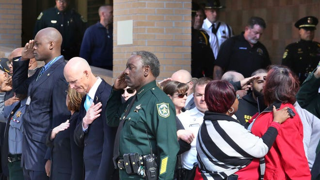 Florida Gov. Rick Scott bows his head and Orange County Sheriff Jerry Demings (center) salutes as the body of an unidentified OCSO deputy is transported from Orlando Regional Medical Center after the deputy was killed while responding to the fatal shooting of an Orlando Police officer in Orlando, Monday, Jan. 9, 2017.