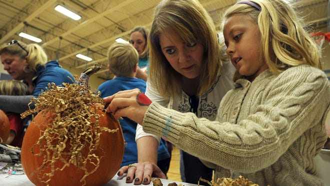 Jennifer Dickey and daughter Olivia Dickey, both of Manitowoc, decorate a pumpkin at Art Along The Lakeshore, part of the annual HarvestFest in Manitowoc in 2014.
