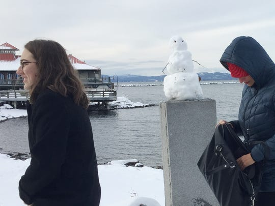 Yolanda Knaak, right, and her daughter, Christina Knaak, stroll past a decrepit snowman Sunday morning along the Burlington waterfront. Photographed Dec. 24, 2017.