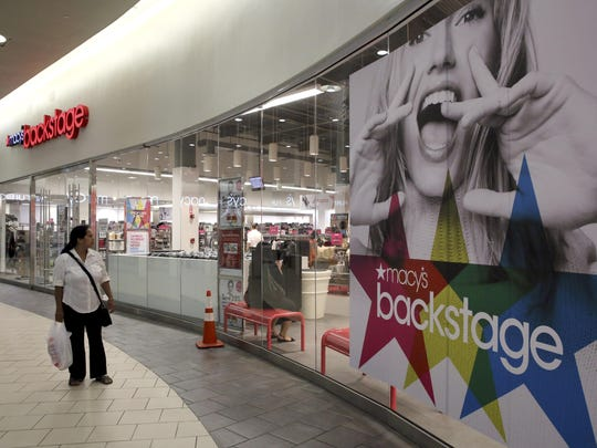 In this Aug. 26 photo, a shopper walks past the Macy's