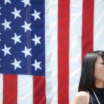 Tomoko Cavagna, who earned her U.S. citizenship in 2015, talks about her journey to the crowd during a celebration on the lawn of the Brown County Courthouse in Green Bay on Saturday.