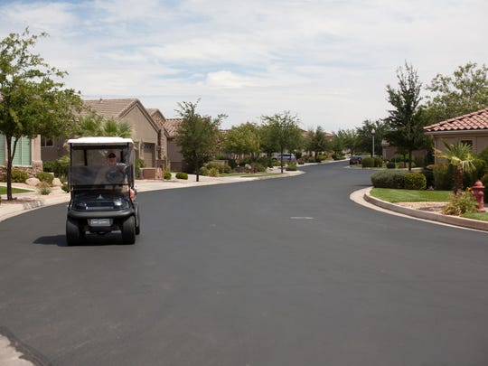 A golfer drives the streets of SunRiver after a round