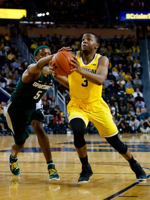 Feb 7, 2017; Ann Arbor, MI, USA; Michigan Wolverines guard Xavier Simpson (3) goes to the basket defended by Michigan State Spartans guard Cassius Winston (5) in the first half at Crisler Center. Mandatory Credit: Rick Osentoski-USA TODAY Sports