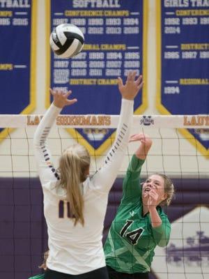 Huntington's Riley Black attempts to hit over Unioto's Amanda McGlone earlier this season at Unioto High School.