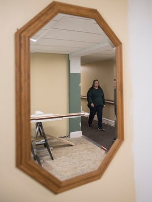 Karen White, who has resided at Hopeton Village for almost three years, walks down the hall to her fifth-floor apartment where construction materials line some of the common areas until work is finished. Many of the residents stay in their apartments at the complex during the live renovation.