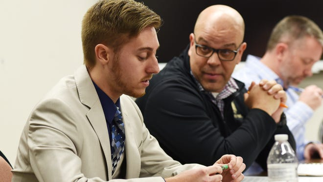 Tri-Valley Local Schools board member Eddie Brock speaks to board member Jason Schaumleffel during a board meeting. Board members have repeatedly asked Jason Schaumleffel  to resign.
