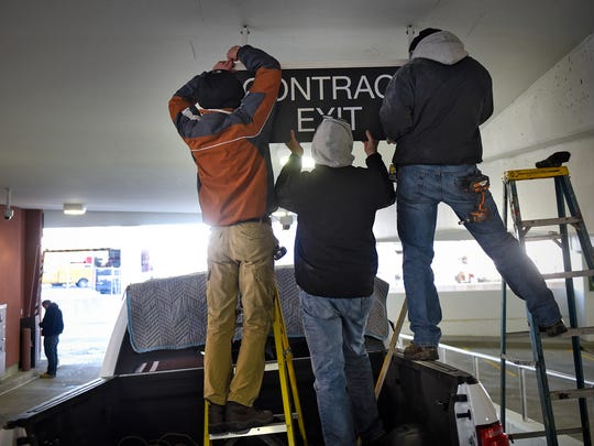 Crews install the final touches, including signage, Monday, Nov. 21,  at the new River's Edge Convention Center parking ramp in St. Cloud. The ramp opened to the public Monday.