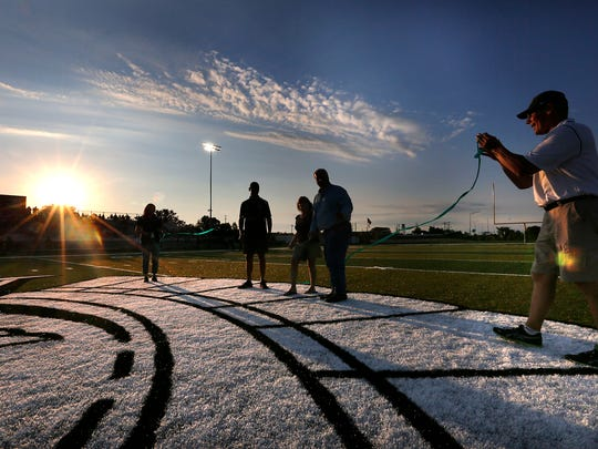As the sun sets, Wauwatosa West athletics director Jeff Gabrielsen (right) holds a ribbon after it was cut before the start of West's game against Tosa East in 2015, the first game on the new turf football field at West.