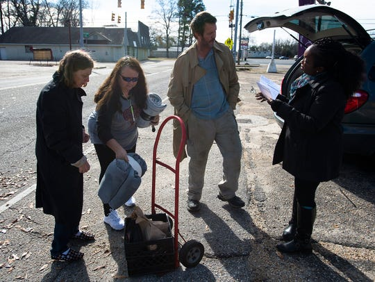 Lakeesa Butler, right, Friendship Mission case manager, fills out paperwork on Jonathan Carswell for the Mid Alabama Coalition for the Homeless count of homeless as Tammy Middleton, Friendship Mission executive director, gives Rachel Carswell a blanket on Wednesday, Jan. 24, 2018, in Montgomery, Ala.