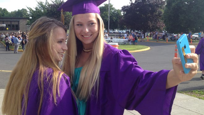 Rhinebeck High School graduates Jamie Stickle and Sonja Reichelt take a cell phone picture together Saturday before graduation.