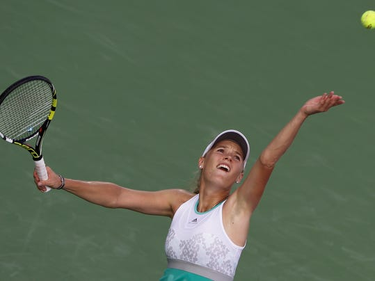 Caroline Wozniacki of Denmark serves the ball to Sabine Lisicki of Germany during the second round of Dubai Duty Free Tennis Championships in Dubai, United Arab Emirates, Tuesday, Feb. 18, 2014. (AP Photo/Kamran Jebreili)