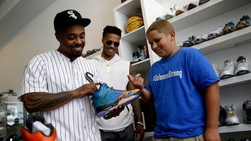 Carl Bradley, left, co-owner of The Luxury Sneaker Exchange on Mass Ave., describes to Jaycob Solomon, right, what all went into Solomon's new custom painted shoes as Indiana Pacers point guard Joe Young watches at The Luxury Sneaker Exchange on Mass Ave. on July 23, 2016. Solomon, who suffered from a dangerous blood disease, was granted his wish of custom shoes by Little Wish Foundation. Pacers point guard Joe Young was on hand to present the shoes. Aside from the shoes, Solomon was given a new bike and an autographed hat from members of his favorite television show Gas Monkey Garage.