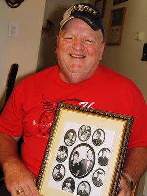 "Charles ""Chip"" Coleman of Sullivanville displays a family photo with his grandparents, in the center, surrounded by their nine sons (including Chip's dad) all of whom served in World War II or the Korean War."