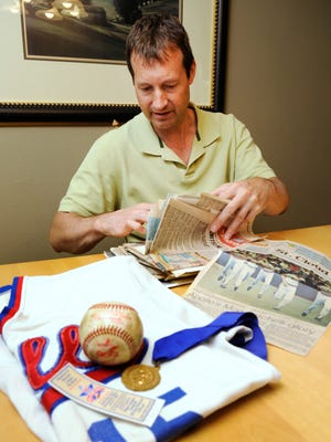 Sean Moe looks through new papers as he talks about shagging balls with the Apollo High School baseball team at the first All-Star Game Home Run Derby