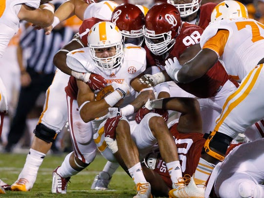Tennessee running back Jalen Hurd (1) is brought down by Oklahoma defenders Dominique Alexander (1), Chuka Ndulue (98) and Jordan Phillips (80) in the second quarter of an NCAA college football game in Norman, Okla., Saturday, Sept. 13, 2014. Oklahoma won 34-10. (AP Photo/Sue Ogrocki)