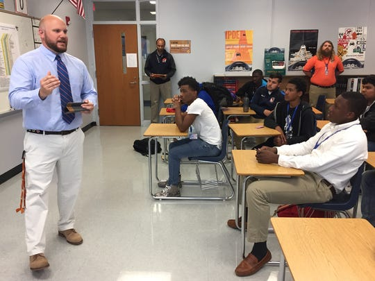 Will Owens, left, talks to the Carolina High football players in April 2018 after being introduced as the school's football coach.
