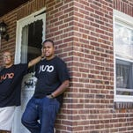 Yuno founder Andre Walters, front, poses for a portrait with his father, Horace, outside their home in the 300 block of W. 36th St. in Wilmington on Thursday. Walters' e-commerce website combines online shopping with social media to reward users who promote products.